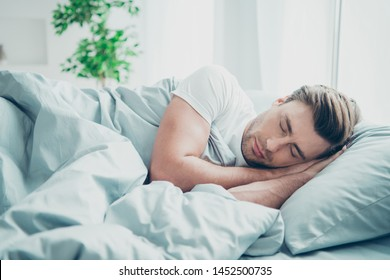 Portrait of cute blonde-haired man lying in bed close eyes indoors room