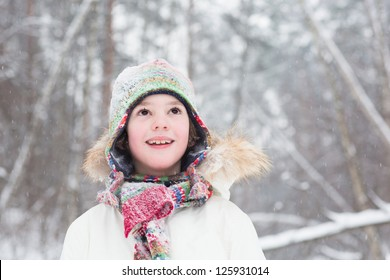 Portrait of a cute boy in a colorful knitted hat and scarf standing in the woods under a snow storm