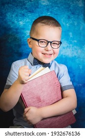 portrait of cute boy with glasses and a shirt with a bow tie holds books, clutching them to himself