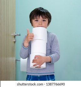 Portrait of cute boy holding toilet roll standing in front of toilet, Child with smiling face showing thumbs up while carrying a stack of toilet paper,