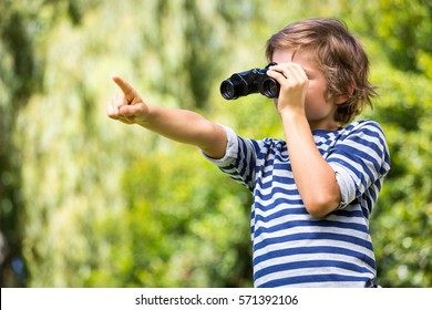 Portrait of cute boy looking with binoculars and pointing something on a park