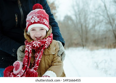 Portrait of a cute boy on a winter day. Son and father spend time in a place in a snow Park.