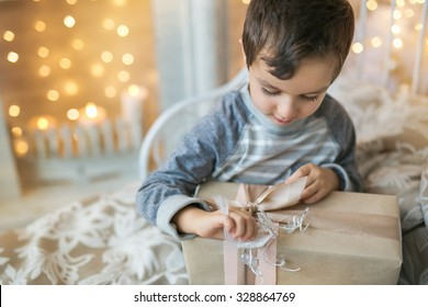 Portrait of a Cute boy in pajamas opens a Christmas gift at home