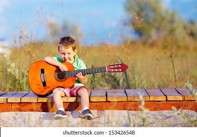 portrait of cute boy playing a guitar on summer field