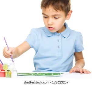 Portrait of a cute boy playing with paints, isolated over white