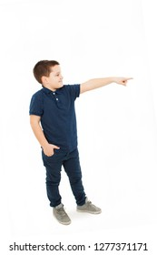 Portrait of a cute boy standing pointing on copy space. Isolated on white background