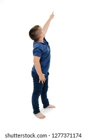 Portrait of a cute boy standing pointing up on copy space. Isolated on white background