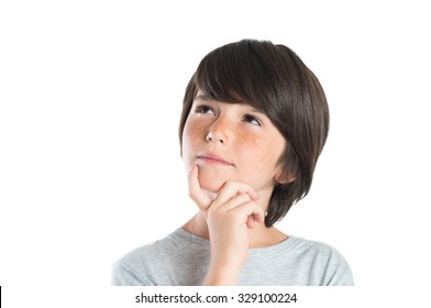 Portrait of cute boy thinking isolated on white background. Closeup shot of boy thinking with hand on chin. Male child with freckles looking up and contemplates isolated on white background.