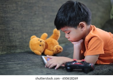 Portrait of a cute boy using a tablet computer in a living room.