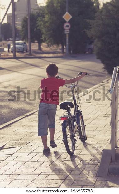 Portrait of a cute boy walk near his bicycle