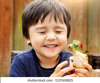 Portrait of cute boy with yummy face enjoy eating roasted chicken drumstick in the garden, Happy kid eating grilled chicken, Healthy picnic food for children concept