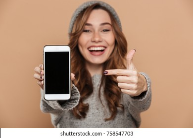 Portrait of cute brunette girl in warm hat and sweater pointing with finger on blank mobile screen, selective focus