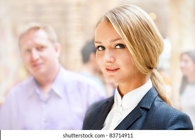 Portrait of a cute business woman with colleagues at the background. Indoors at modern office building center