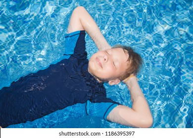 Portrait of cute calm blond white kid relaxing in clear blue water of outdoors sunny swimming pool lying calmly on back. Horizontal color photography.