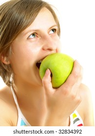 Portrait of a cute  Caucasian blond girl with a nice colorful striped dress who is smiling and she is biting a fresh green apple. Isolated on white.