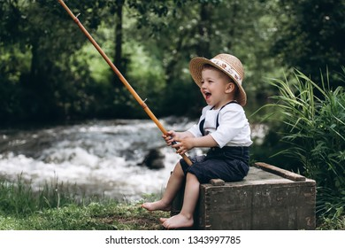Portrait of cute caucasian blondie baby boy with fishing rod in country side background. Nature, outdoors, childhood concept