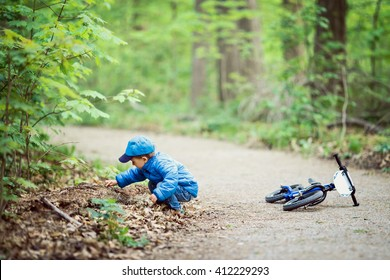 Portrait of cute Caucasian little boy toddler in blue jacket, jeans and baseball cap with bike in park playground outside, sitting on ground discovering learning new, happy childhood lifestyle concept