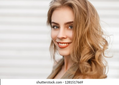 Portrait of a cute charming girl with a wonderful smile with natural make-up with curly hair with blue eyes on a white background. Happy positive young woman. Close-up.