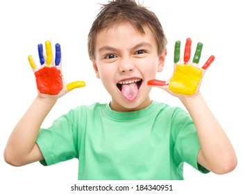 Portrait of a cute cheerful boy showing his hands painted in bright colors and sticking out tongue, isolated over white