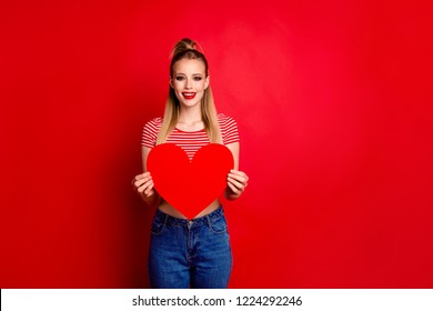 Portrait of cute cheerful charming attractive magnificent good-looking girl with pony-tail holding in hands big paper heart isolated over bright vivid red background