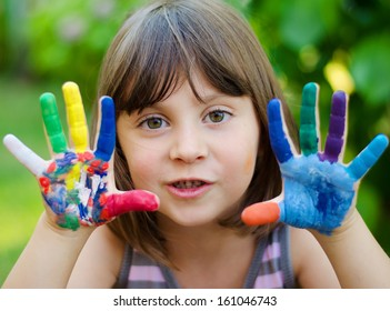 Portrait of a cute cheerful girl with painted hands