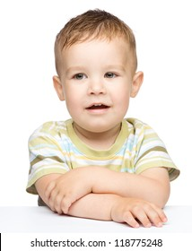 Portrait of a cute cheerful little boy, who is smiling while sitting at table, isolated over white