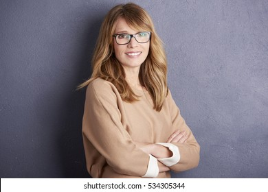 Portrait of a cute cheerful middle aged woman looking at camera and smiling while standing by the wall.
