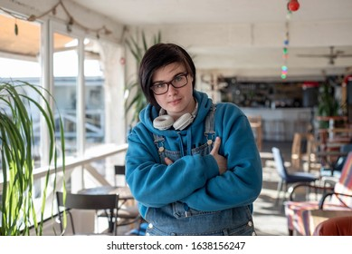 Portrait of a cute and cheerful neutral gender teenager, in a sunlit room in a cafe