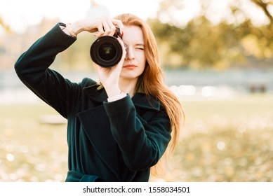 portrait of cute cheerful young girl with amazing red hair posing outdoors holding camera, redhead woman is relaxing on the park