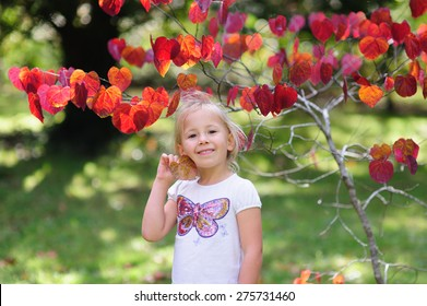 A portrait of a cute child, adorable little girl with blonde hair holding a heart shaped leaf standing in front of a pretty tree with red leaves in a garden