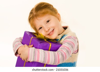 Portrait of cute child with big violet giftbox smiling and looking at camera