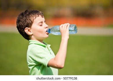 Portrait of a cute child drinking water from a bottle outdoor