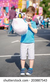 Portrait of cute child eating cotton candy over a summer fair festival background