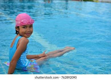 Portrait of cute child girl in the swimming pool. she wearing blue swimsuit , pink bathing cap and goggles over clear water with copy space for text.