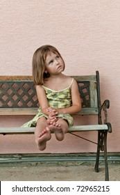 Portrait of cute child sitting on bench and stretching barefoot legs