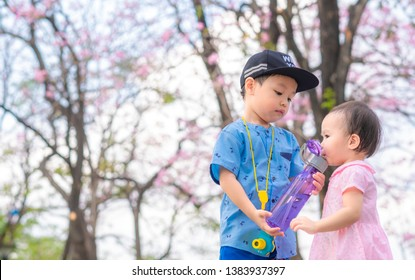 Portrait of a cute child sucking water from plastic bottle with tube at flower garden. little boy shares his plastic bottle with a girl. Soft focus.  Copy space.
