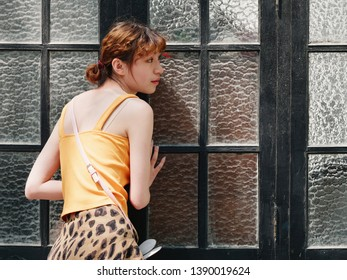 Portrait of cute Chinese girl in yellow sundress eavesdropping behind glass windows.