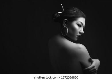 portrait of a cute chinese woman with a fashionable black make-up on a dark background