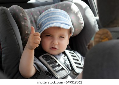 Portrait of cute cool toddler boy sitting in car seat with a lovely smile on his face. Child transportation safety, family travel concept