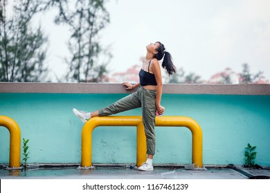 Portrait of a cute, cool, young and attractive Japanese Asian girl stretching and posing against a colorful wall in a city. The young teenager is tanned, athletic, cool and beautiful.