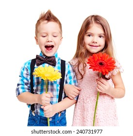 Portrait of cute couple of children with flowers in hands
