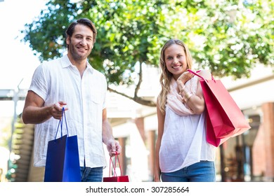 Portrait of a cute couple holding shopping bags