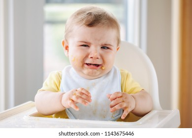 Portrait of cute crying Caucasian child boy with dirty messy face sitting in high chair after eating apple puree with fingers. Everyday home childhood lifestyle. Infant trying supplementary baby food