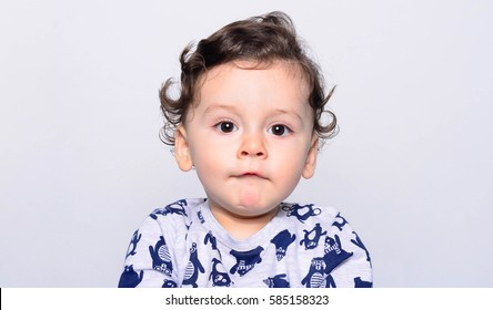 Portrait of a cute curly hair baby boy. Adorable one year old child looking funny and curious. Baby boy with big eyes.