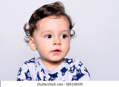 Portrait of a cute curly hair baby boy looking away. Adorable one year old child looking funny and curious to the side. Baby boy with big eyes and open mouth showing his teeth.