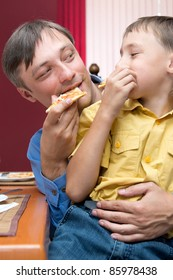 portrait of a cute dad and son eating pizza