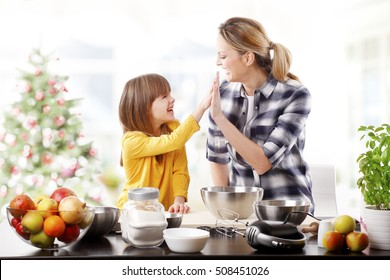 Portrait of cute daughter and her mom giving each other a high five while baking christmas cookies together in the kitchen.
