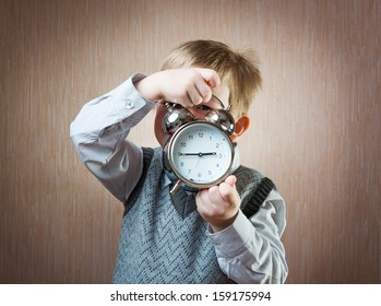 Portrait of cute diligent boy holding alarm clock