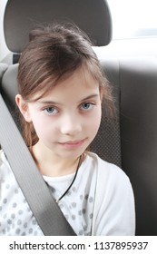 Portrait of cute elementary age young girl sitting in car wearing a seat belt. Child transportation safety concept.
