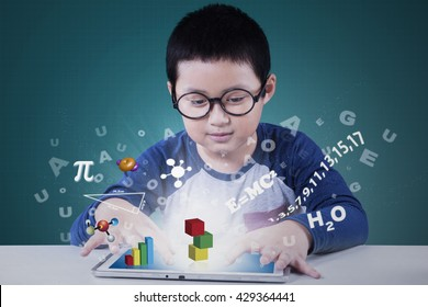 Portrait of a cute elementary school student using application on the tablet for studying